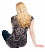 Back view of beautiful young woman sitting on the floor and looks into the distance. Blonde girl rel