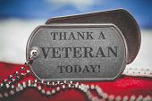 Worn US American dog tags on USA flag with Thank a Veteran Today engraved text poster