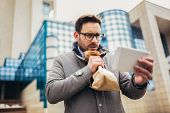 Businessman Holding Paper Bag Over Mouth As If Having A Panic Attack And Looking In Digital Tablet. poster