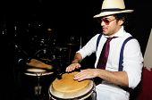 Portrait of young male percussionist playing cuban drums against black background