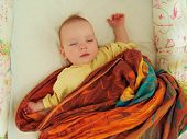 The Little Baby Sleeps Sweetly In His Crib In A Plaid, In A Sling, In A Blanket. The Baby Girl Sleep poster