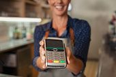Waitress at cash counter holding an electronic card payment machine. Close up of mature woman hand h poster