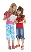 Full length photo of two little girls standing, holding tablet and smart phone, isolated on white.
