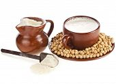 powdered milk drink in clay pitcher , soy beans and cup on white background