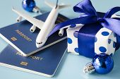 Christmas Or New Year Travel Concept. Toy Airplane With Passports And Gift Box On Blue Background. poster