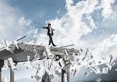 Businessman Walking Blindfolded Among Flying Documents On Concrete Bridge With Huge Gap As Symbol Of poster