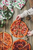 Three Pizzas Lie On A Wooden Table Against The Background Of Christmas Decor. Top View Of Three Pizz poster