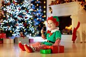 Kids At Christmas Tree. Children Open Presents poster