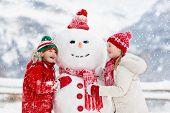 Child Building Snowman. Kids Build Snow Man. poster