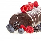 Chocolate biscuit roll cake roulade with fresh berries isolated on white