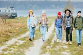 Group Of Five Hikers Travel Peole In Bright Casual Wear And With Backpacks On Coast Of Lake. Best Fr poster
