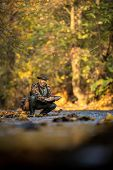 Handsome fly fisherman working the line and the fishing rod while fly fishing on a splendid mountain poster