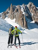 Two mountain touring skiers in front of the breathtaking view of Mont Blanc de Tacul, Mont Blanc Massif, Western Alps, France, Europe.