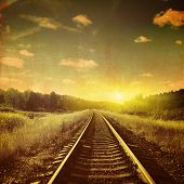 Sunset over railroad in grunge and retro style.