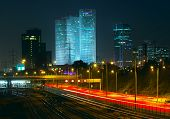 Night view of Tel Aviv city downtown, illuminated Azrieli towers and light traces on Ayalon highway.