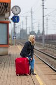 a young woman with luggage waiting on the platform of a railway station for their train. train delay