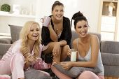 Girls together at home, watching tv in pyjamas, smiling happy.