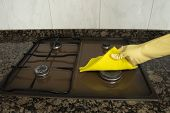 woman cleaning Stove in the kitchen with yellow cloth