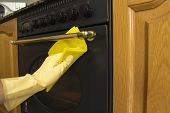 Female arms cleaning the outside of an oven