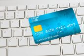 stock photo of plastic money  - blue  plastic card  on modern keyboard  - JPG