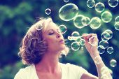 a beautiful woman blowing bubbles