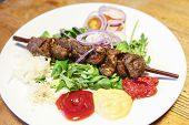 Pork shashlik (skewer) on white plate