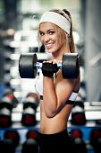 Smiling athletic woman pumping up biceps in a gym