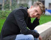 stock photo of sad eyes  - Serious or sad blond young man in jeans and jacket sitting outdoors looking in camera - JPG