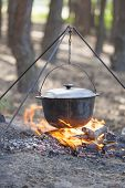 stock photo of cauldron  - Camping kettle over burning campfire in forest - JPG