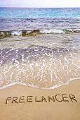 Word Freelancer Written In Sand, On A Beautiful Beach