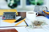 Office supplies with money and cup of coffee on table on bright background