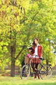 Young woman with bicycle in a park reading a book