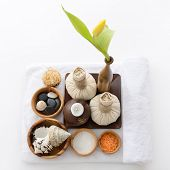 spa still life with spa herbal balls, candlestick, tulip, stones and salt in wooden bowl and white t