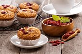 Vegan muffins with dried cranberries on wooden table