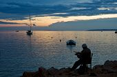 NOVALJA, ISLAND PAG, CROATIA - CIRCA SEPTEMBER 2010 - Man fishing on sunset