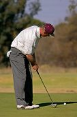Man putting on the green during a golf match