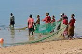 Mozambican fishermen and women pulling a fishing net from the water