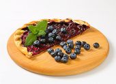 half of cake with fruit filling and with fresh blueberries, served on a wooden cutting board