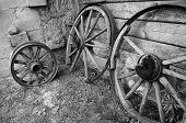 Old wooden wheels of cart at a barn wall.