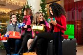Diversity group of four people - Caucasian, black and Asian - sitting with Christmas presents and ba