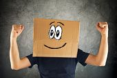 Happy Smiling Man With Cardboard Box On His Head And Raised Fists