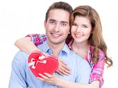 Happy young couple with a gift in a studio isolated on a white background.