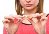 image of addiction to smoking  - Young woman is breaking a cigarette - JPG