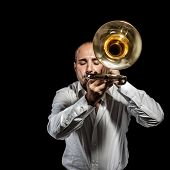 foto of trombone  - a young jazzer with a trombone over black background - JPG