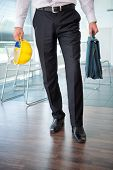 Legs of business man holding hard hat and briefcase in office