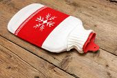 picture of hot-water-bag  - Hot water bottle or bag on wooden background - JPG