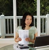 Mature Woman Working At Home Office With Tax Forms