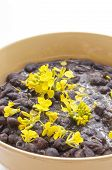 stock photo of phaseolus  - Closeup of bowl of black turtle beans garnished with yellow mustard flowers