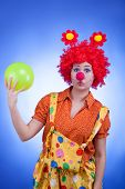 Sad Clown With A Ball In Hands On Blue Background