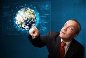 Businessman standing and touching high-tech 3d earth panel